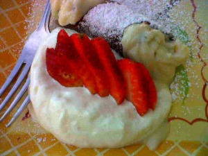 Chocolate covered canolli with fresh cream and strawberries.