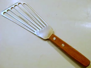 Fish spatulas—elongated versions of a burger/pancake flipper. Designed for being able to easily get underneath delicate fillets without breaking them up or tearing the crispy skin you love to eat. This esscential kitchen tool is perfect for removing vegetables from a baking sheet along with transferring fresh-baked pastries from oven to cooling rack.